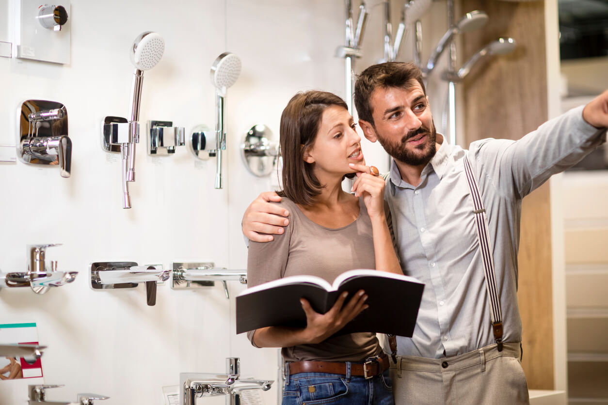 Husband and wife going over the catalog booklet while shopping for bathroom equipment in a lavatory equipment store.
