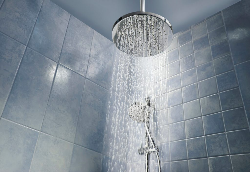 Low angle of running water from shower head in a cool coloured shower