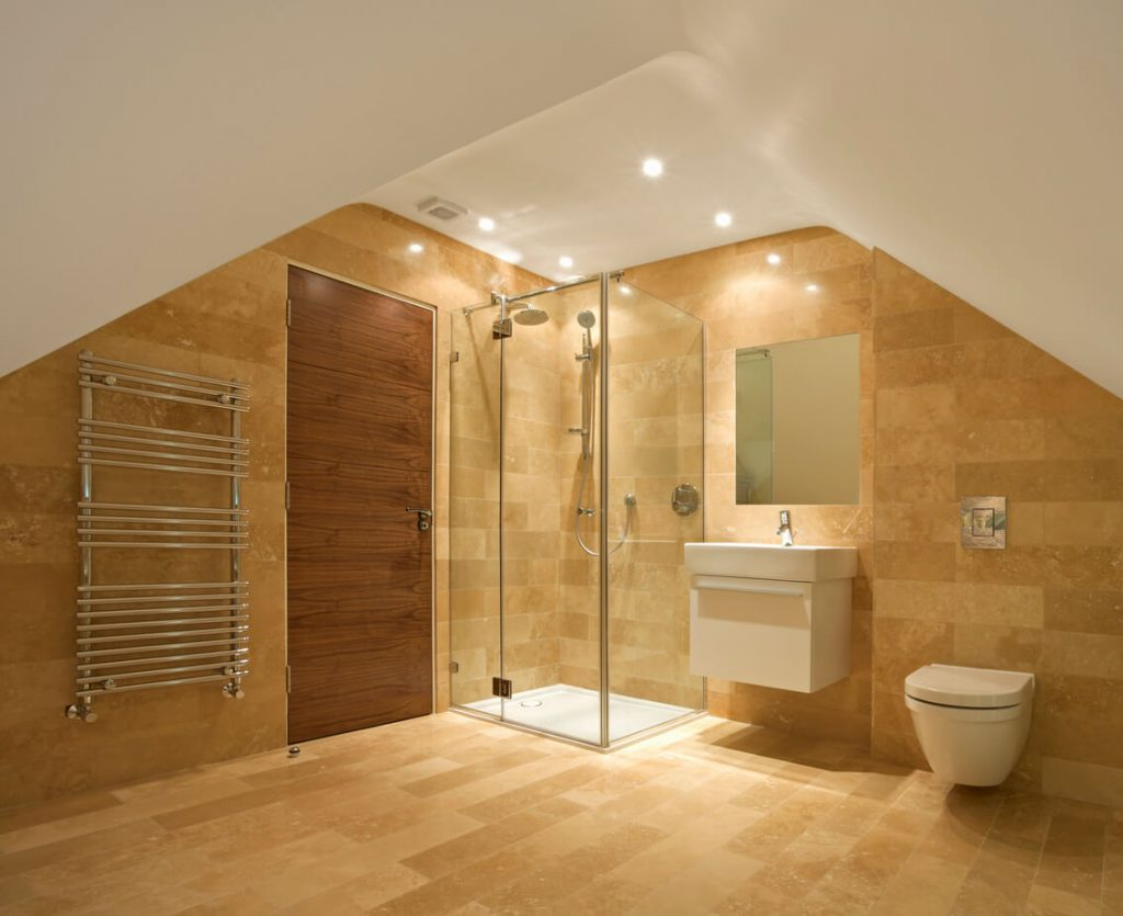 a bathroom in the attic of an expensive new home. A shower unit sits in the centre with fixed and hand shower. To the left of the solid walnut door is a modern towel radiator. To the right of the shower is a handwash basin and toilet. The walls and flooring are lined with natural stone.