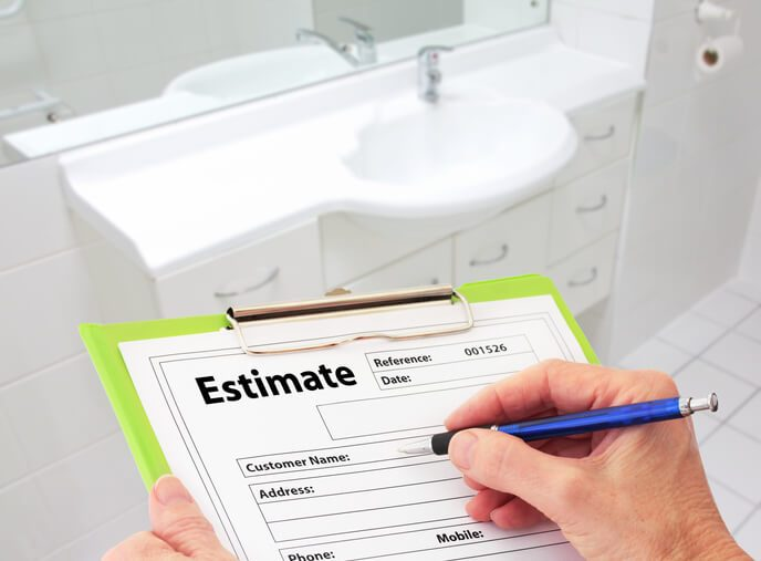 Hand writing an estimate on a clipboard to renovate a bathroom