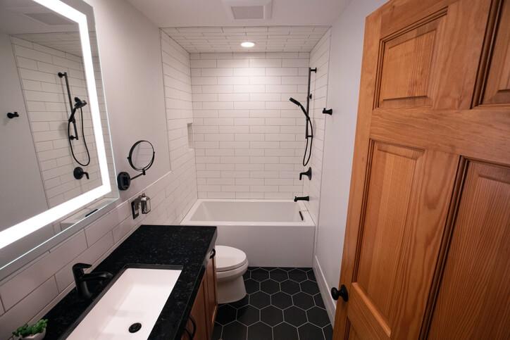 Modern Bathroom with Deep Bathtub and Black Hexagonal Floor Tiles and Matte Black Fixtures