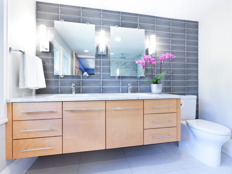 Contemporary interior bathroom design with glass enclosed shower stall with Cararra marble tiles. Duo shower heads with rain shower and conventional shower head. White Cararra marble counter and natural wood vanity. Heated towel rack hanger. Photographed in horizontal format.