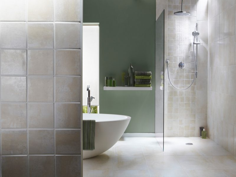 The interior of a simple, modern walk in shower bathroom in a cool, green tone. There is a bath, shower, a bath towel . There are light grey tiles in the shower with running water