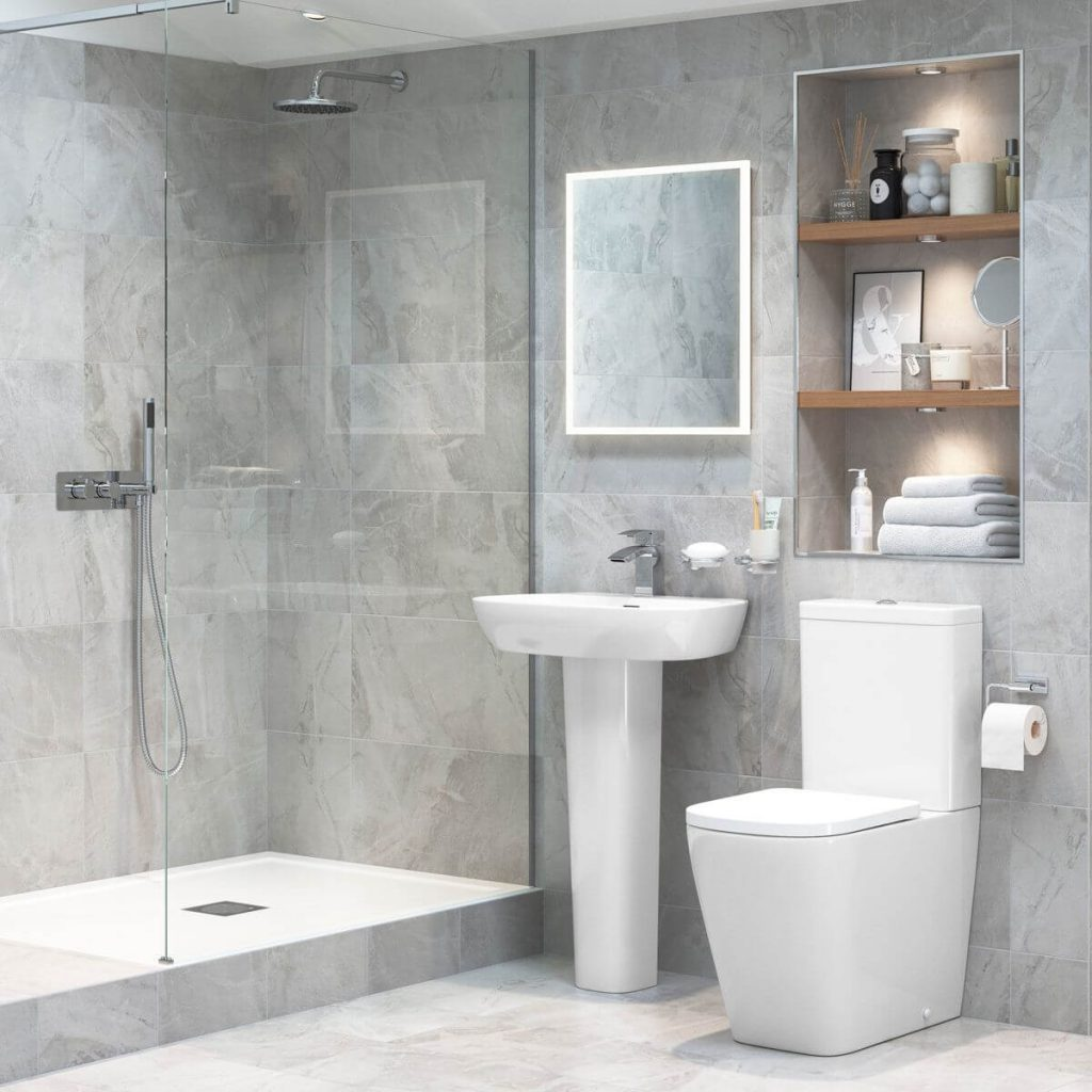 Toilet and basin with mirror above in a grey tiled cloakroom