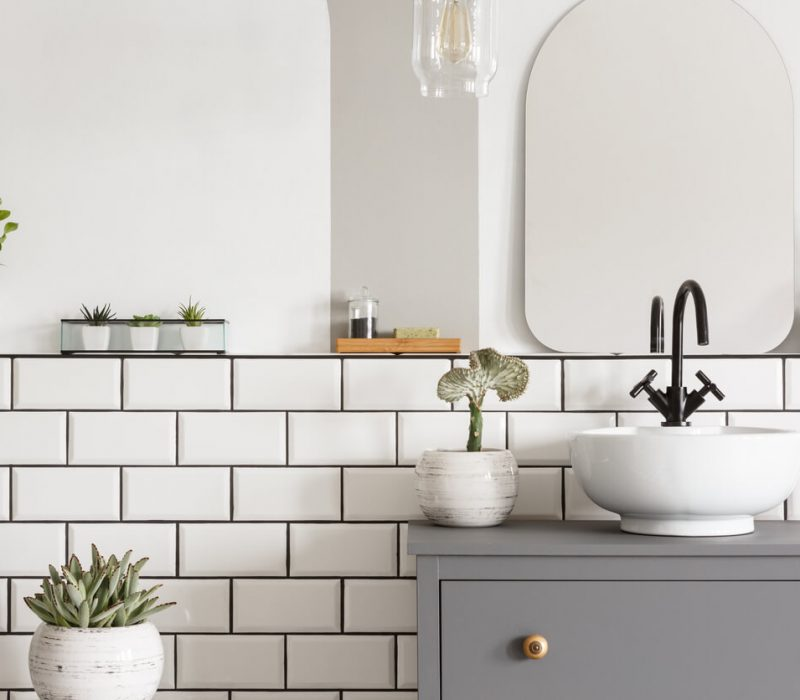 Real photo of a white sink on a grey cupboard in a bathroom interior with tiles, mirror and plants