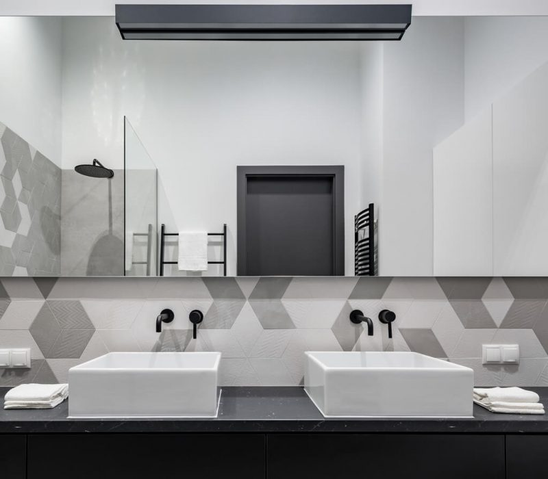 jack and jill bathroom in black, white and gray with two washbasins and big mirror