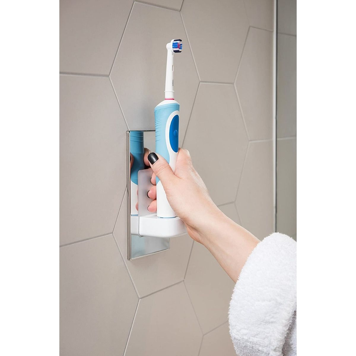 A woman putting the oral b electric toothbrush back on charge